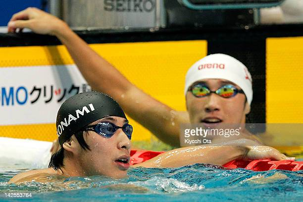 Takuro Fujii reacts next to Kazuya Kaneda after competing in the Men's 100m Butterfly semi final during day six of the Japan Swim 2012 at Tokyo...