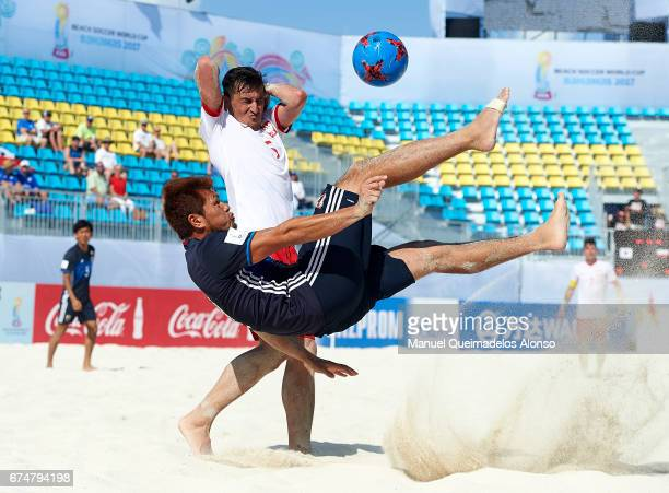 Takuya Akaguma of Japan attempts a scissor kick shot on goal in front Tomasz Lenart of Poland during the FIFA Beach Soccer World Cup Bahamas 2017...