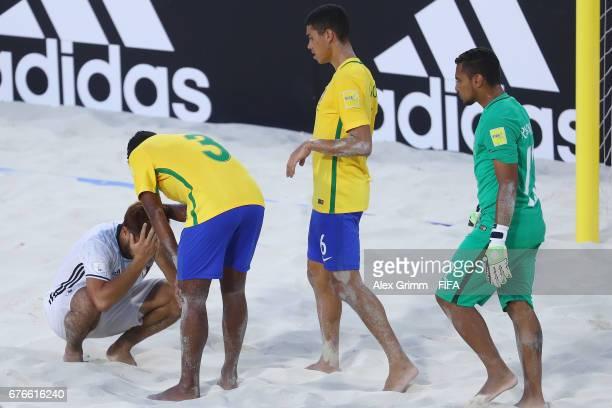 Takuya Akaguma of Japan is comforted by Filipe Lucao and Rafa Padilha of Brazil after the FIFA Beach Soccer World Cup Bahamas 2017 group D match...