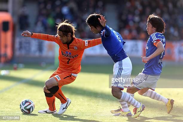 Takuya Honda of Shimizu SPulse competes for the ball against Kosuke Nakamachi and Shunsuke Nakamura of Yokohama FMarinos during the JLeague match...
