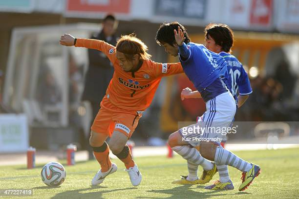 Takuya Honda of Shimizu SPulse keeps the ball under the pressure from Shunsuke Nakamura and Kosuke Nakamachi of Yokohama F Marinos competes for the...