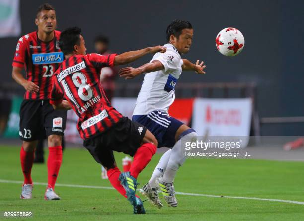 Takuya Kida of Yokohama FMarinos controls the ball under pressure of Chanathip Songkrasin of Consadole Sappporo during the JLeague J1 match between...