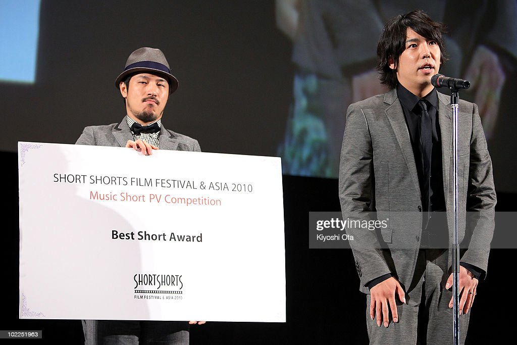 Takuya Ohashi (R) of jazz fusion duo Sukima Switch speaks next to Shintaro Tokita of jazz fusion duo Sukima Switch as they receive the 'Music Short PV Competition Best Short Award' for director Yuki Iwata's film '8mm' during the Short Shorts Film Festival & Asia 2010 Award Ceremony at Jingu Kaikan on June 20, 2010 in Tokyo, Japan. The annual festival is one of the Asia's largest festivals for international short films, and the Grand Prix winner, selected from the three official Best Short Award winners, will be eligible for an Academy Award nomination in the Short Films category.
