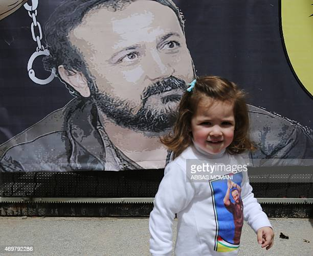 Tala the granddaughter of Fatah leader Marwan Barghuti stands in front of a poster bearing his portrait during a march to mark the anniversary of his...