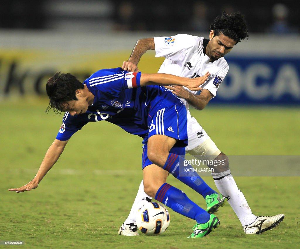 Talal Al Bloshi of Qatar's Al-Sadd club (R) challenges Yeom Ki-Hun of South Korea's Suwon Samsung Bluewings during their AFC Champions League semi-final football match at Al-Sadd stadium in Doha, on October 26, 2011. Suwon won 1-0.