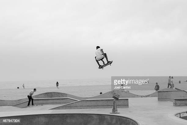 Talented teenage skateboarder mid-air at Venice Beach Skate Park