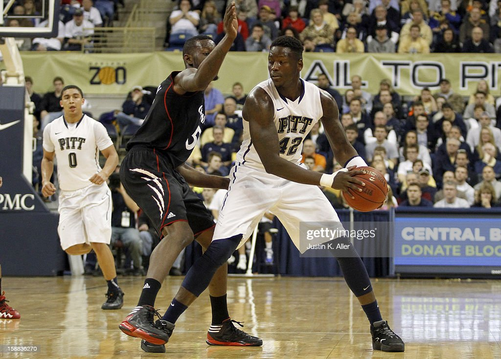 Talib Zanna #42 of the Pittsburgh Panthers protects the ball from Justin Jackson #5 of the Cincinnati Bearcats at Petersen Events Center on December 31, 2012 in Pittsburgh, Pennsylvania.