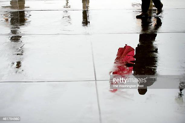 Talibah Morgan of Washington DC seen in reflection make her way through rainy streets outside Union Station on January 12 2015 in Washington DC