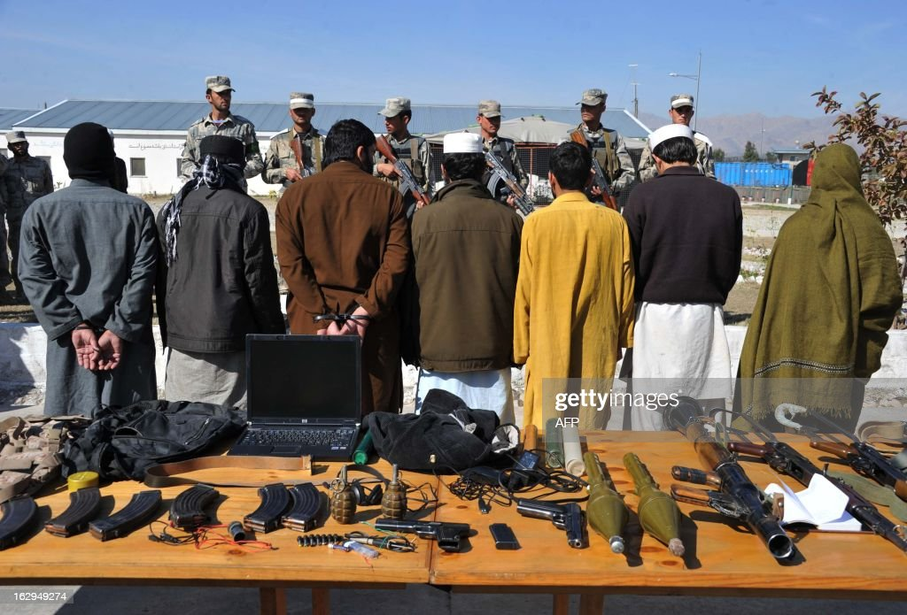 Taliban fighters stand handcuffed near seized weapons as they are displayed to the media at a police headquarters in Jalalabad on March 2, 2013. Seven Taliban insurgents have been arrested with their weapons by Afghan border police during an operation in Ghani khel District of Nangarhar province. AFP PHOTO/ Noorullah Shirzada