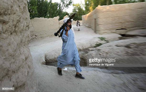 A taliban insurgent serving under Mollah Najib's command in Andar district Ghazni province provides security during one of his meetings while they...