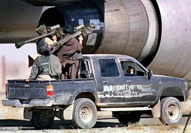 Taliban Islamic militia commandos riding on a pickup truck pass an engine of the hijacked Indian Airlines plane with US made heat seeking surface to...