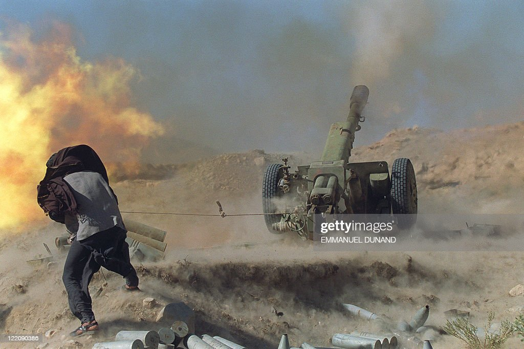Taliban Moslem militia gunner fires a 122mm Howitzer 10 November 1966 on the frontline some 30 kilometers north of Kabul on rival faction infantry...