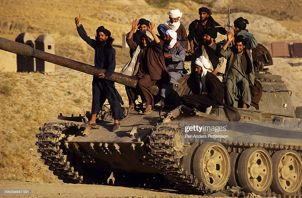 Taliban soldiers on a tank outside Kabul