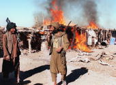 Taliban soldiers stand guard as a heroin making factory goes up in flames in the southern Sarhadi district of Helmand 27 October 2000 Afghan's ruling...