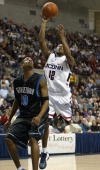 Taliek Brown of the UCONN Huskies shoots over Darrel Owens of the Georgetown Hoyas January 14 2004 at the Gampel Pavilion in Storrs Connecticut UCONN...