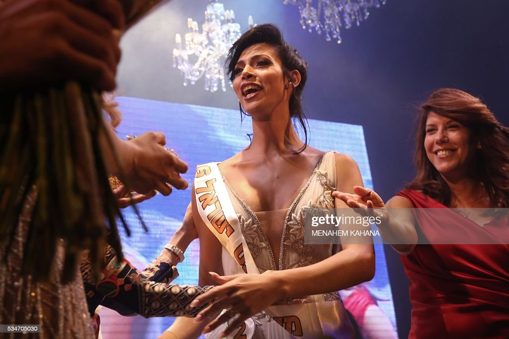 Talin abu Chana (C), 21, a Christian Arab-Israeli from Northern Israel, reacts upon winning Israel's first Miss Trans beauty pageant at Habima national theater in Tel Aviv on May 27, 2016, which marks the beginning of the 2016 Pride events. / AFP / MENAHEM