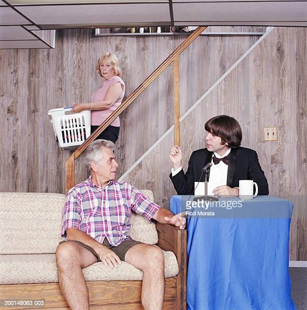 Talk show host interviewing mature man in basement