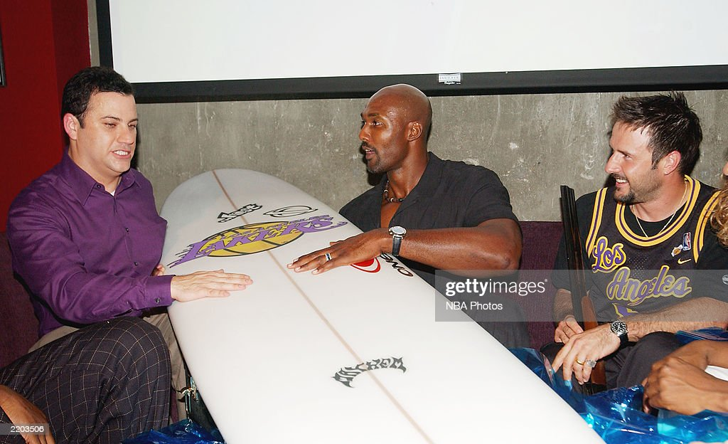 Talk show host Jimmy Kimmell, basketball player Karl Malone and actor David Arquette laugh at Karl Malone's gift at a party held for Gary Payton and Karl Malone celebrating both Los Angeles Lakers players' birthdays at the Lucky Strike on July 24, 2003 in Los Angeles, California.