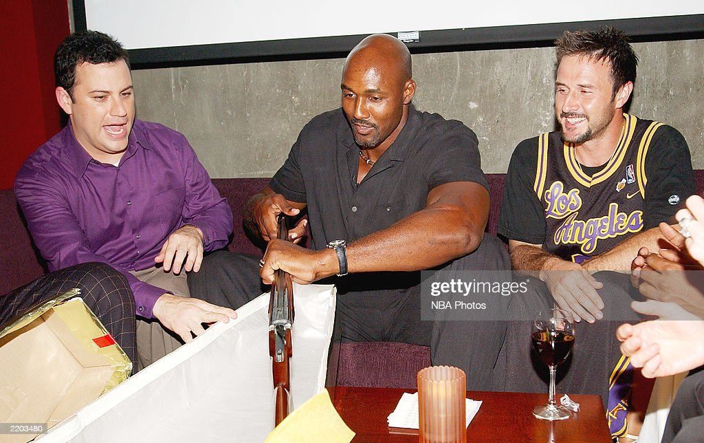 Talk show host Jimmy Kimmell, basketball player Karl Malone and David Arquette have a laugh as Karl Malone receives one of many shotguns that were given to him as gifts at a party held for Gary Payton and Karl Malone celebrating both Los Angeles Lakers players' birthdays at the Lucky Strike on July 24, 2003 in Los Angeles, California.