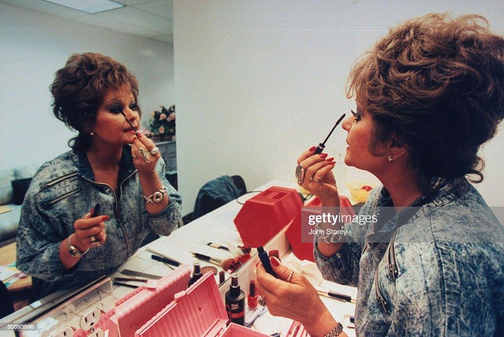 TV talk show host Tammy Faye Bakker Messner applying mascara to eyelashes in mirror in dressing room.