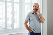 Man talking on the phone. He is standing by the window in his home with a serious expression.
