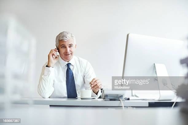 CEO talking on the phone while having coffee