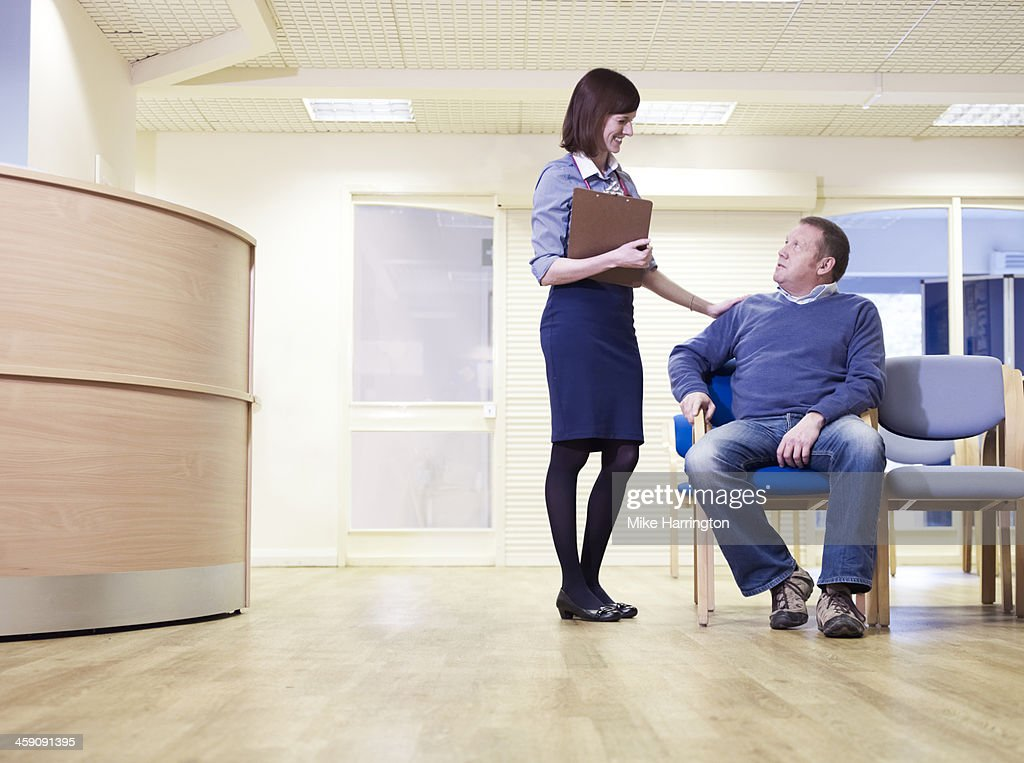 GP talking to patient in surgery waiting room.