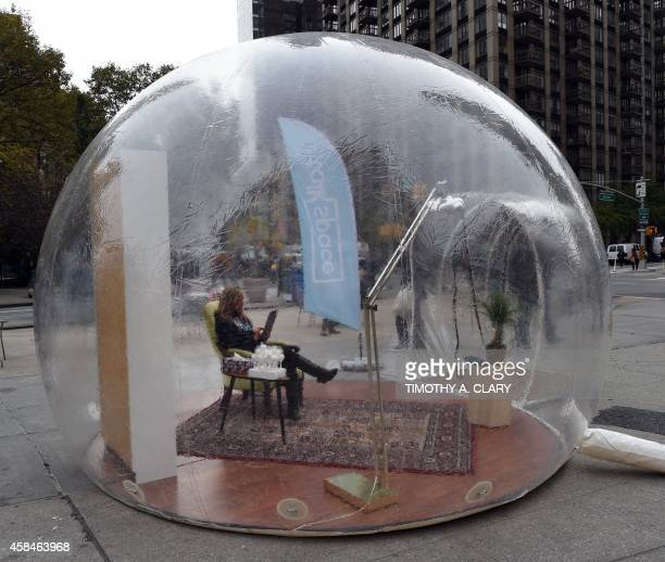 Talkspace therapist Christy Paul LMHC texts with a patient from a plastic bubble set up in New York November 5 during the kickoff of the Talkspace...