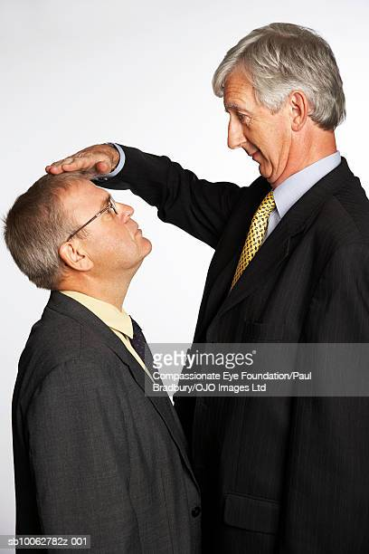 Tall and short businessmen comparing height, profile