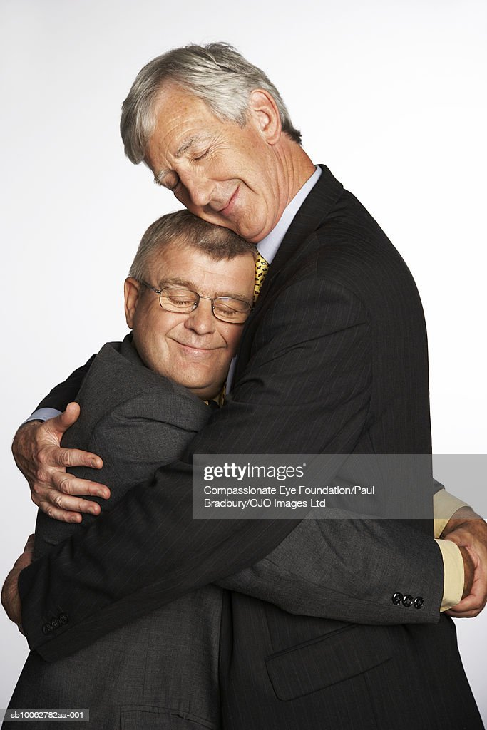 Tall and short businessmen hugging, side view : Stock Photo