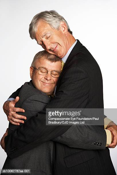 Tall and short businessmen hugging, side view