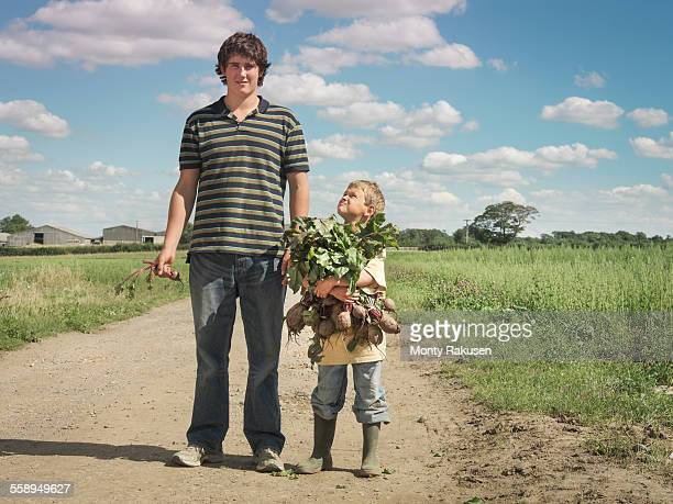 Tall and smaller farmers sons carrying armful of organic beetroot