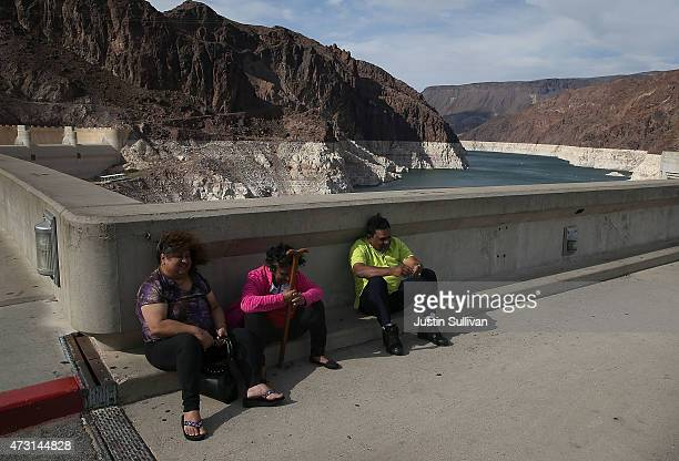 A tall bleached 'bathtub ring' is visible behind visitors that are taking shelter from the wind while visiting the Hoover Dam on May 12 2015 in Lake...