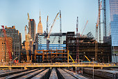 tall buildings under construction and cranes under a blue sky in New York City