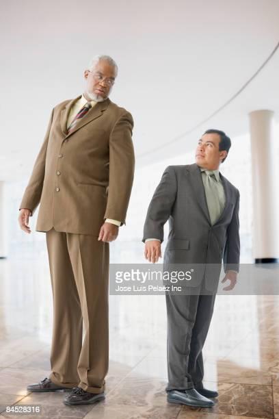 Tall businessman looking down at short businessman