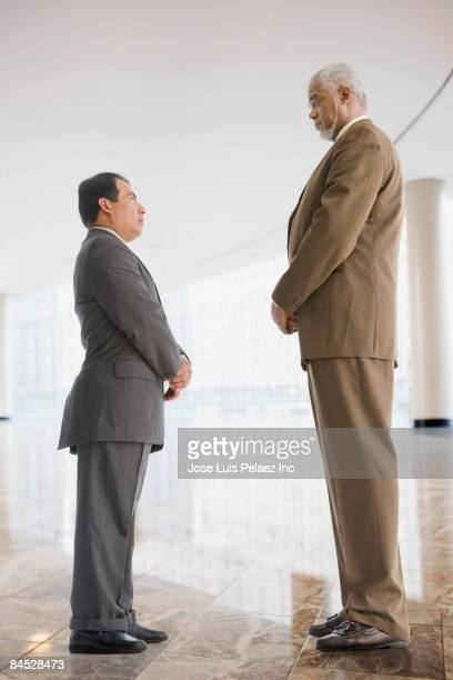 Tall businessman looking down at short businessman