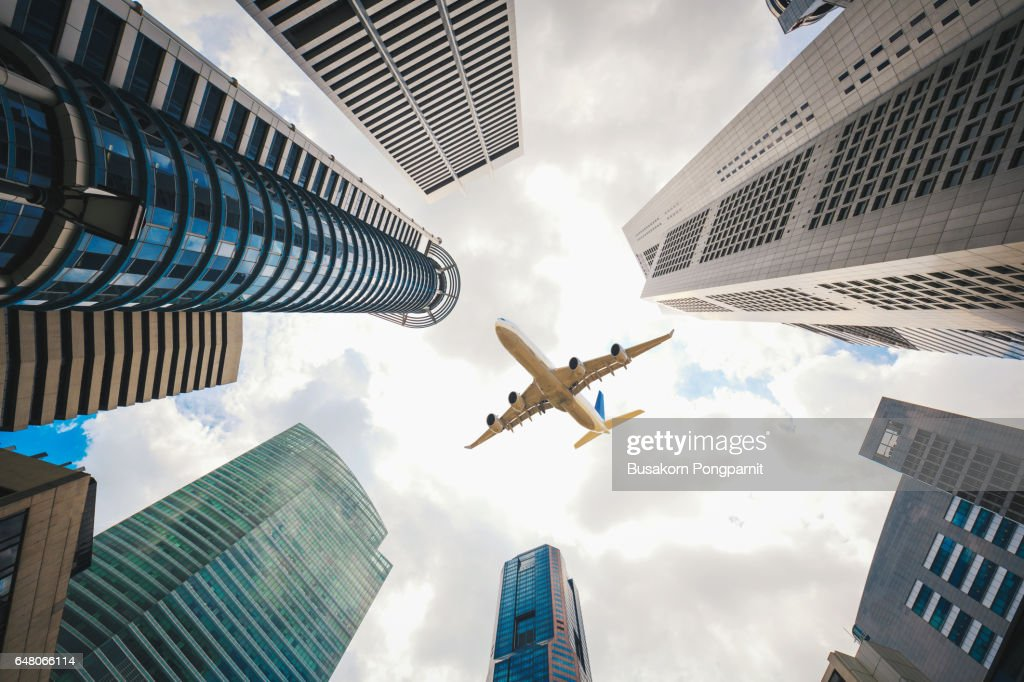 Tall City Buildings And A Plane Flying Overhead Stock Photo