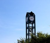 A tall green clock tower and the bright blue clear sky in the background.