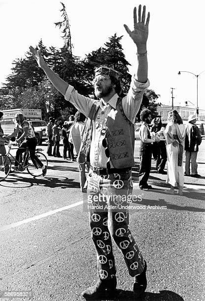 A tall hippie wearing peace symbols on his pants at a demonstration protesting the war in Vietnam San Francisco California late 1960s