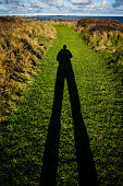 Tall shadow of a man on a grass path.  Image taken in Northern Ireland (Kearney, County Down) in the autumn/fall, where the sun's elevation is low at this time of year, creating long shadows in the la