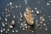 A tall ship is escorted by tens of smaller ships on its way to Amsterdam where it will take part in Sail Amsterdam 2010 Replicas of a Russian frigate...