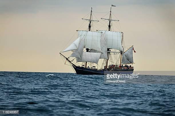 Tall ship sailing into sunset, Cornwall - UK