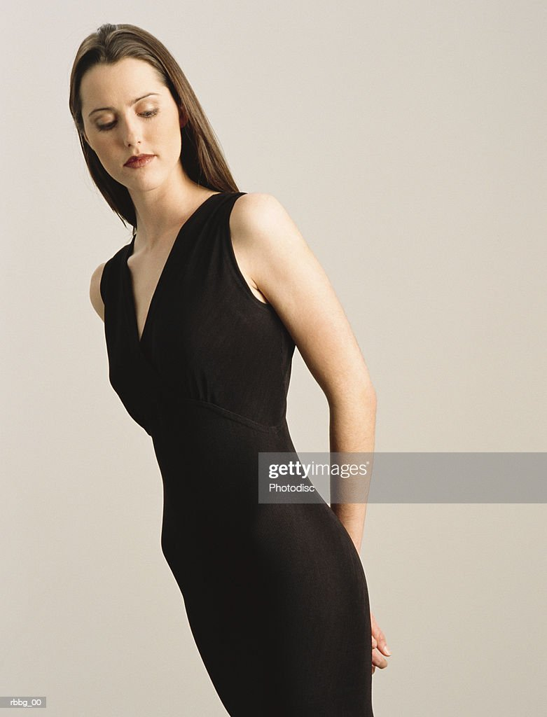 tall slender woman in a tight black dress standing against a gray background looking at the ground