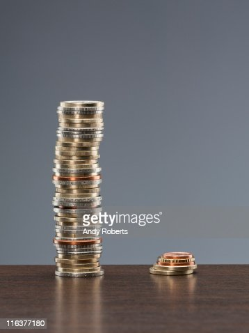 Tall stack of coins next to short stack of coins : Stockfoto