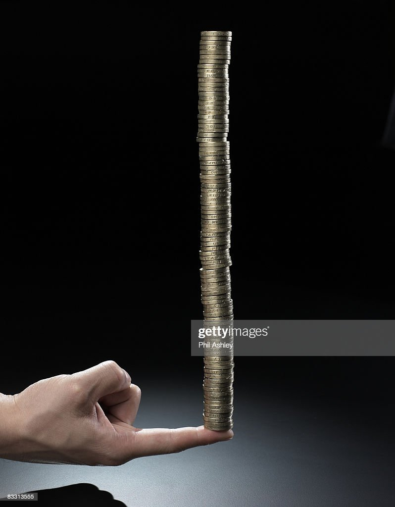 tall stack of gold coins balancing on one finger : Stock Photo