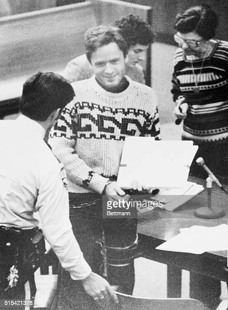 Suspected mass killer Theodore R Bundy with legal files in hand and a puzzling smile on his face is escorted from the Leon County Courthouse after a...