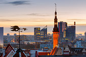 Weather vane in the form of a cock over an old city against a background of modern buildings at sunset. Tallinn. Estonia.