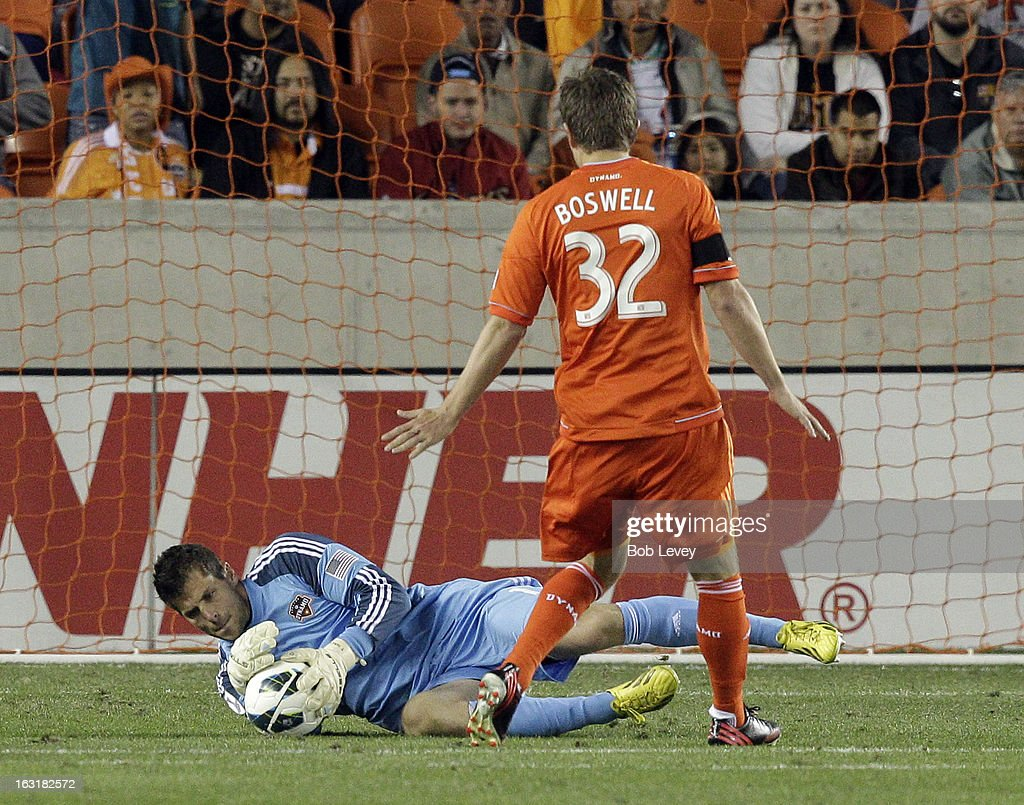 Tally Hall #1 of Houston Dynamo makes a save against Santos Laguna as <a gi-track='captionPersonalityLinkClicked' href=/galleries/search?phrase=Bobby+Boswell+-+Soccer+Player&family=editorial&specificpeople=587535 ng-click='$event.stopPropagation()'>Bobby Boswell</a> #32 of Houston Dynamo makes sure there is no rebound during the second half at BBVA Compass Stadium on March 5, 2013 in Houston, Texas.