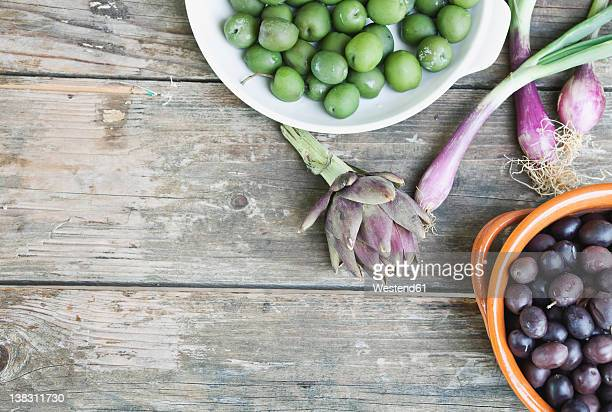 taly, Tuscany, Magliano, Olives in bowl, spring onions and artichoke on wooden table