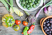 taly, Tuscany, Magliano, Olives in bowl, spring onions, tomatoes, peppers and artichoke on wooden table